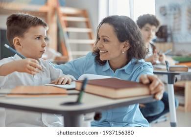 Happy kind teacher is helping kids in elementary school lessons