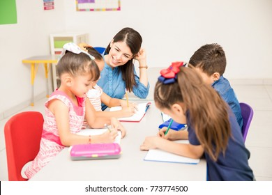 Happy kindergarten female teacher helping her students with some writing exercise in the classroom