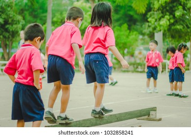 Happy Kindergarten students are exercising in morning.