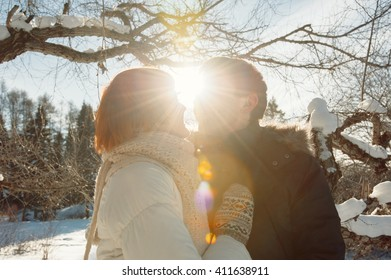 Happy kissing couple on winter park background at sunlight
