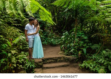 Happy kissing multiracial  couple hugging on walking trail in tropical forest. Young mixed race couple on honeymoon in Asia. Romantic relationship. Love story. Jungle rainforest. Ubud, Bali, Indonesia
