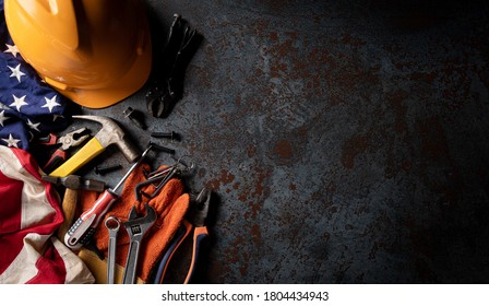 Happy Labor day concept. American flag with different construction tools on dark stone background, with copy space for text.