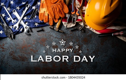 Happy Labor day concept. American flag with different construction tools on dark stone background, with Happy Labor Day text.