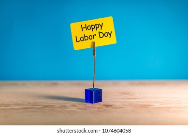Happy labor Day - message on pinned yellow note at blue background. Labour day celebrated at May 1. Spring time