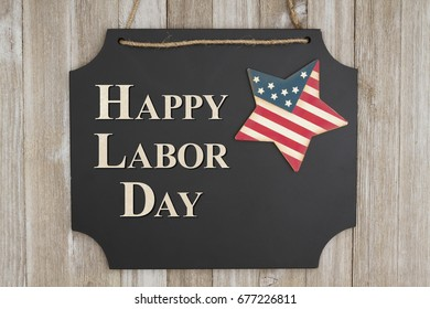 Happy Labor Day text on hanging chalkboard with a flag star on weathered wood wall