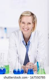 Happy laboratory technician or technologist standing behind a counter filled with chemical solutions and glassware looking at the camera with a beautiful smile on her face