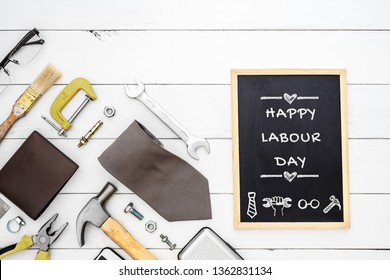 Happy Labour Day background concept. Flat lay of construction blue collar handy tools and white collar's accessories over wooden background with black chalkboard and Happy Labour Day text.