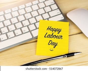 Happy Labour day on sticky note on work table