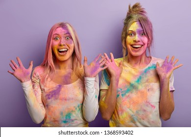Happy ladies look similar, have coated skin with colourful powder, show mulitcolored palms, celebrate Holi holiday on March, come on dynamic Color Festival in India, splash dyes on each other
