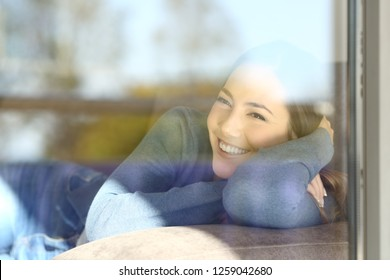 Happy lady looking through the window lying on a couch at home