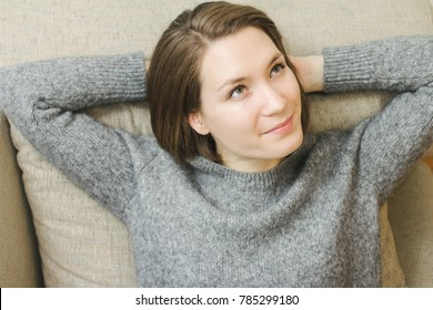 Happy lady lying down on comfortable pillows daydreaming thinking at home beautiful young caucasian woman
