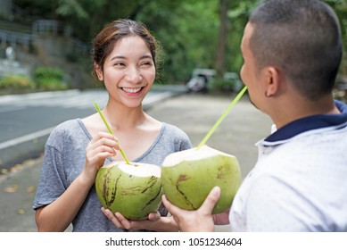 Happy lady and a man refreshing with coconut juice. Outdoor summer picture.