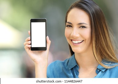 Happy lady showing a blank phone screen mock up in the street