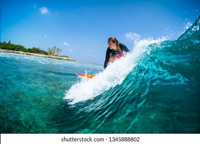 Happy lady surfer rides the tropical wave at sunny day