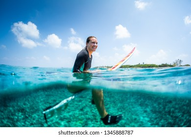 Happy lady surfer sits on the surfboard and waits the wave. Splitted image with underwater view