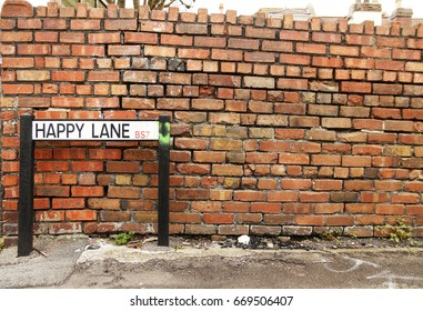 Happy Lane - Quirky British road sign in front of a brick wall in Bristol UK