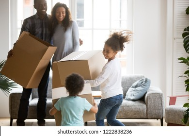 Happy large African American family just moved in new house, embracing parents standing, looking at playing toddler son and daughter carrying boxes, unpacking boxes with belongings, moving concept