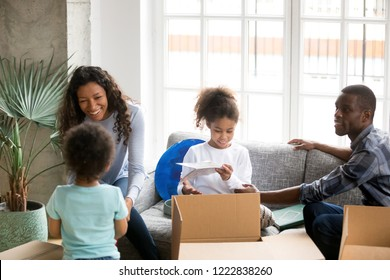 Happy large African American family unpacking cardboard boxes with belongings, just moving, sitting together on couch, little daughter and toddler son helping parents with packaged things, new home