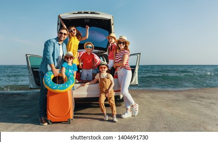 happy large family mother father and children in summer auto journey travel by car on beach
