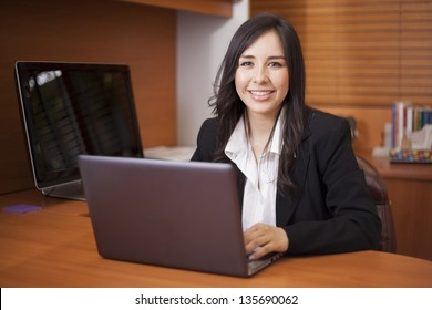 Happy latin businesswoman doing some work