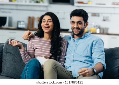 happy latin couple watching tv at home with bowl of popcorn