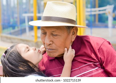 Happy latin granddaughter giving a kiss to her grandfather wearing hat.