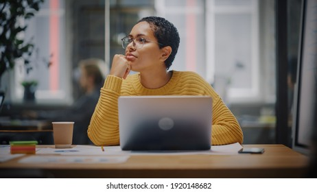 Happy Latin Marketing Specialist in Glasses Working on Laptop Computer in Busy Creative Office. Beautiful Diverse Female Project Manager Hesitating and Thinking Before Answering an Email to Colleague.