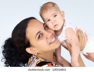 Happy latin mother carrying her baby girl