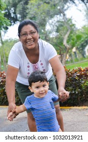 Happy latin mother with her little son in the summer park.