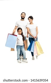 happy latin parents holding shopping bags while standing with cute daughter isolated on white