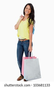 Happy Latin student with shopping bags against white background