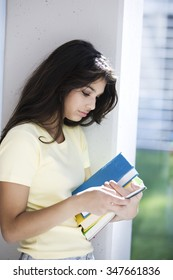 Happy latin teen student with books and mobile phone
