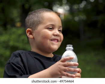Happy Latino boy holding a plastic water bottle