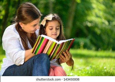 Happy latino family reading book at park