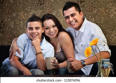 Happy Latino family of three embracing on a sofa