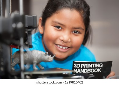 A happy latino girl is proud of her 3d printed toy and is holding a 3d printing handbook as part of a STEM summer camp.