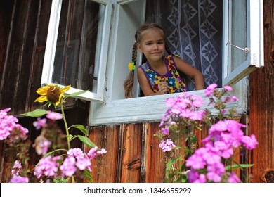 Happy laughing 5-6 years old girl opening a window in the house in village to meet a new day, happy summertime concept, vacation in the village