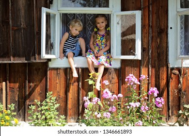 Happy laughing 5-6 years old girl and her little brother sitting on the window sill in the house in village to meet a new day, happy summertime concept, vacation in the village