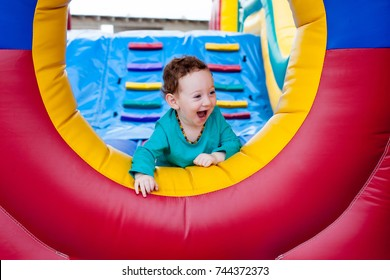 Happy laughing adorable toddler peeking out on trampoline