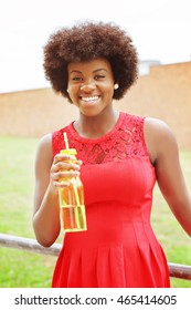 Happy laughing african girl with bottle of water