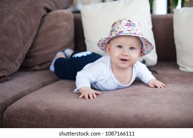 Happy laughing baby boy lying on sofa at home with funny hat on head
