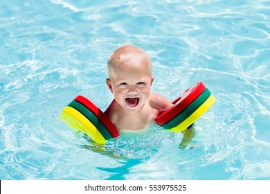 Happy laughing baby boy playing in outdoor swimming pool on a hot summer day. Kids learn to swim. Child with colorful armbands. Family vacation in tropical resort