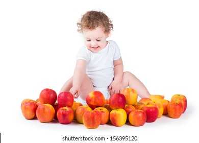 Happy laughing baby girl playing with red and yellow apples on white background