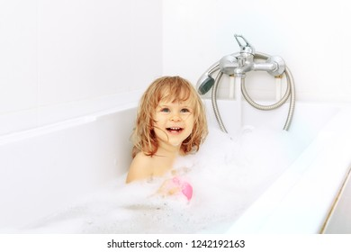 Happy laughing baby taking a bath playing with foam bubbles. Little child in a bathtub. Smiling kid in bathroom with colorful toy duck. Infant washing and bathing. Hygiene and care for young children.