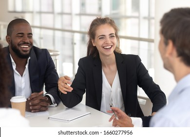 Happy laughing black man and woman break in business negotiations. Fun smiling african american businessman and white businesswoman at meeting with partner and investors, female and male relationship