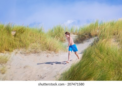 Happy laughing boy, active child running, playing and jumping in sand dunes on the North Sea, Holland on a sunny hot summer day with beautiful blue sky having fun during vacation