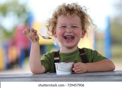 A happy, laughing boy is eating chocolate ice cream out of a cup and with a plastic spoon. He has blonde curly hair