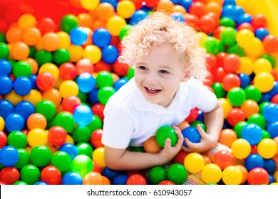 Happy laughing boy having fun in ball pit on birthday party in kids amusement park and indoor play center. Child playing with colorful balls in playground ball pool. Activity toys for little kid