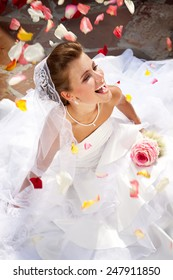 Happy Laughing Bride Sitting Outdoors on the Floor with Colorful Petals