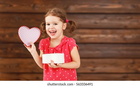 happy laughing child girl with gift Valentine's Day, wooden background